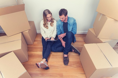 Young couple packing and sitting next to moving boxes